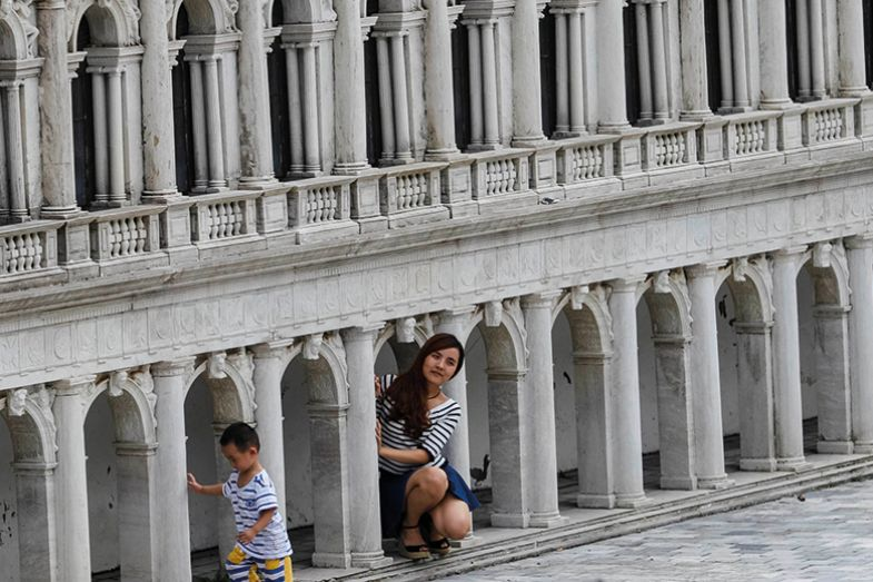 "A woman poses near the Venetian Saint Mark's Square miniature in the theme park ""Window Of The World"" in Shenzhen, Guangdong province, China, October 20, 2014"