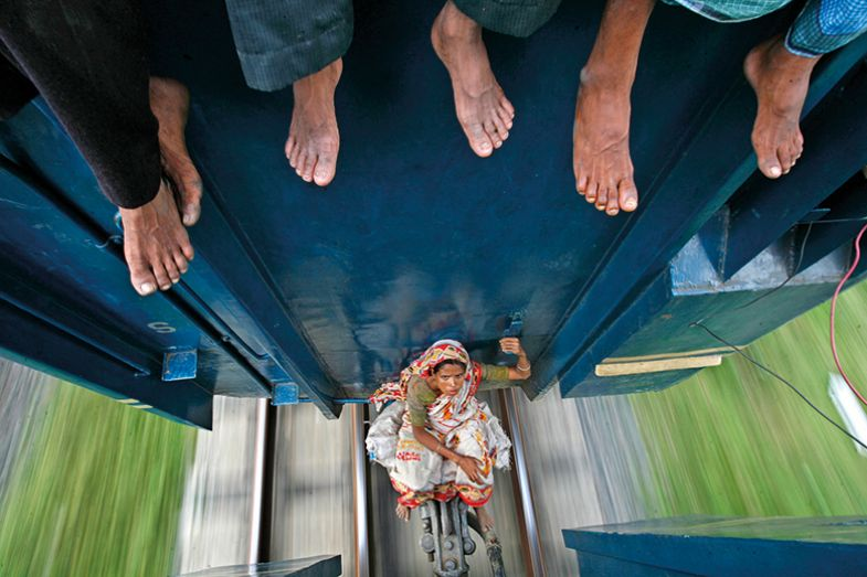 A woman sits between carriages as the train travels to Mymensing from Dhaka September 20, 2009.