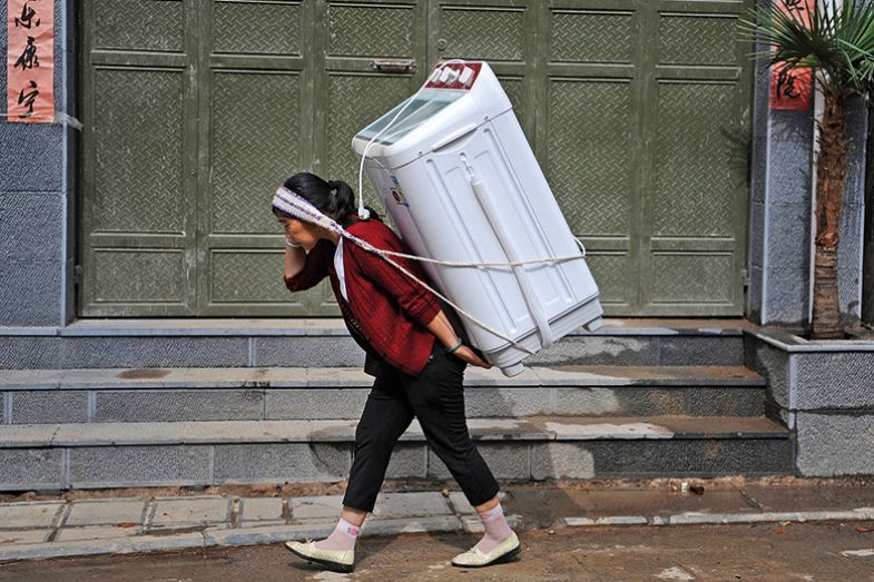 A woman carries home a washing machine in Dali, Yunnan province July 30, 2013.