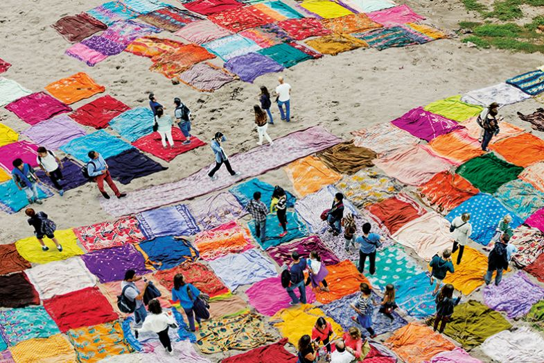Montage of people walking over saris on beach