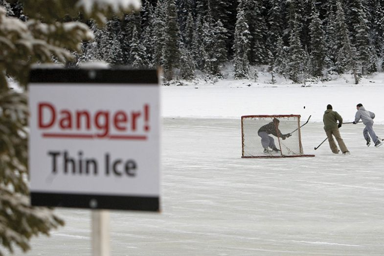 "A group of skaters play pond hockey on Lake Louise, with a ""Danger! Thin ice"" sign."
