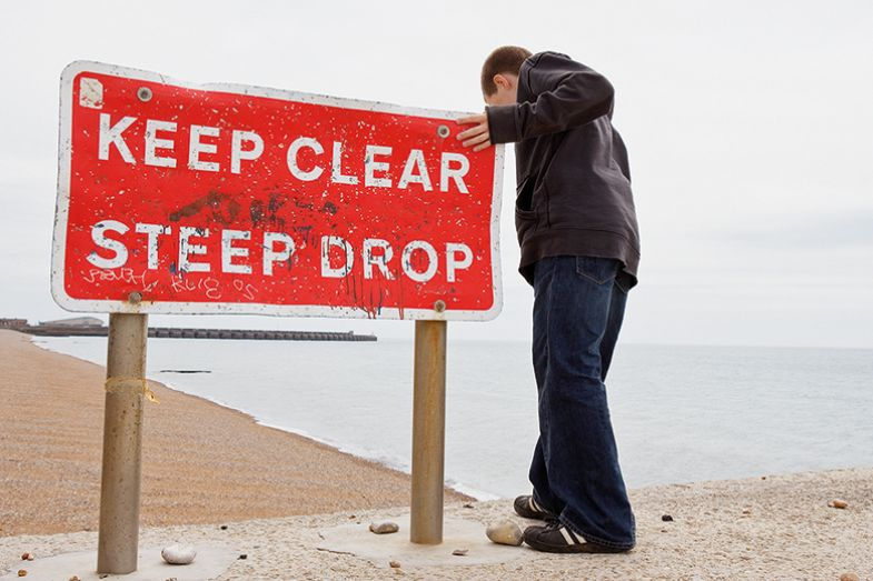 "Person near edge with ""Keep Clear. Steep drop"" sign"