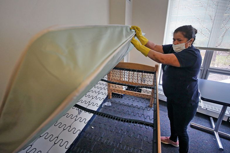 A cleaning company employee inspects a bed in a dorm unit of a university during the coronavirus pandemic