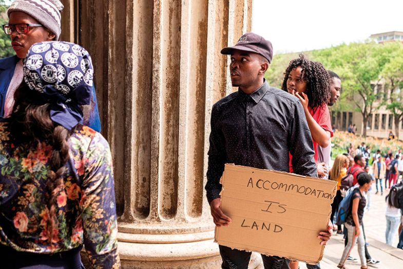 """A student holds a placard that reads """"Accommodation is Land"""" on the WITS University Campus in Johannesburg's central suburb of Braamfontein"""