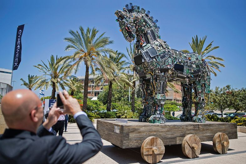 A man photographs 'Cyber Horse', a replica of the Trojan horse by 'No, No, No, No, No, Yes' and made of computer and mobile phone components infected with viruses and malware, Tel Aviv, 2016