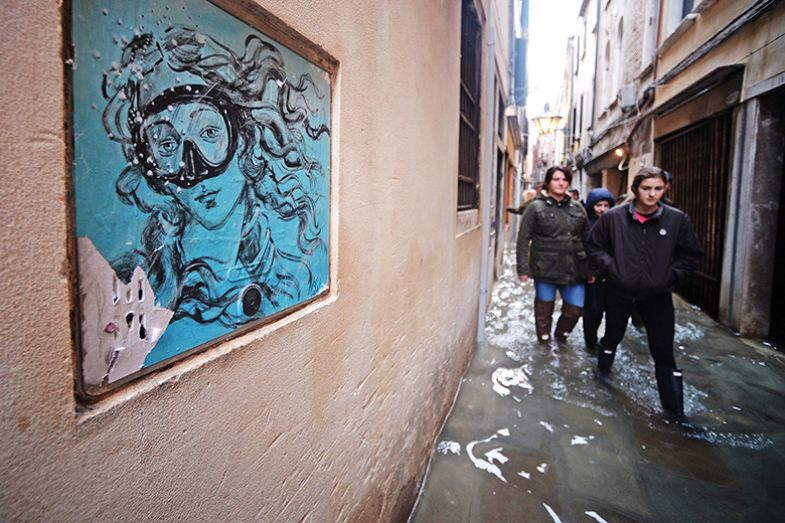 "People walk in a flooded street in Venice, during ""acqua alta"", or high water, of 160 centimetres (over five feet), on November 17, 2019"