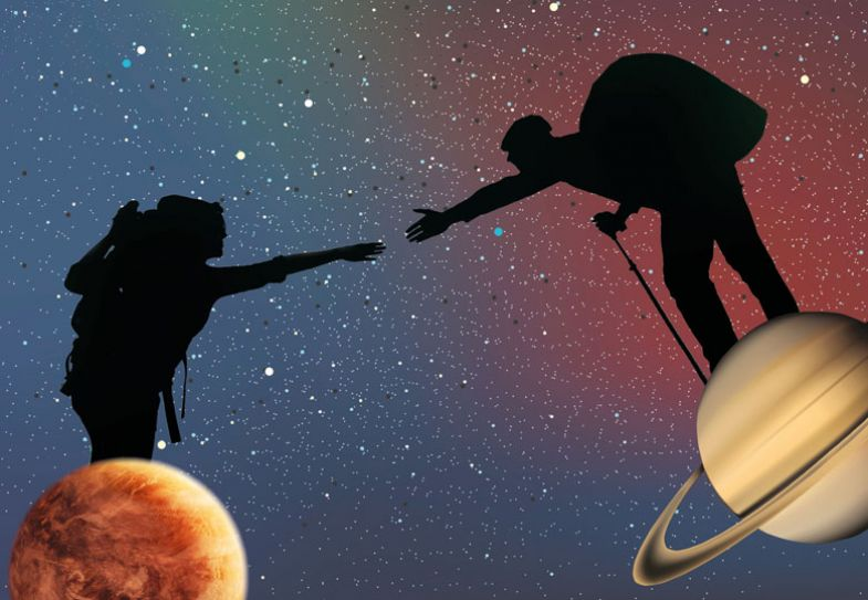 Silhouette of two people reaching out to each other, each standing on a different planet.