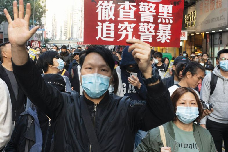 Pro-democracy protesters march on a street as they take part in a demonstration on December 8, 2019 in Hong Kong, China to describe up to 2019 the mask was a symbol of resistance, worn by protesters
