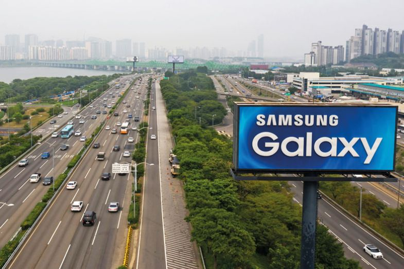 An advertisement for Samsung Electronics Co. Galaxy smartphones stands next to vehicles traveling along the road in an aerial photograph taken in Seoul, South Korea