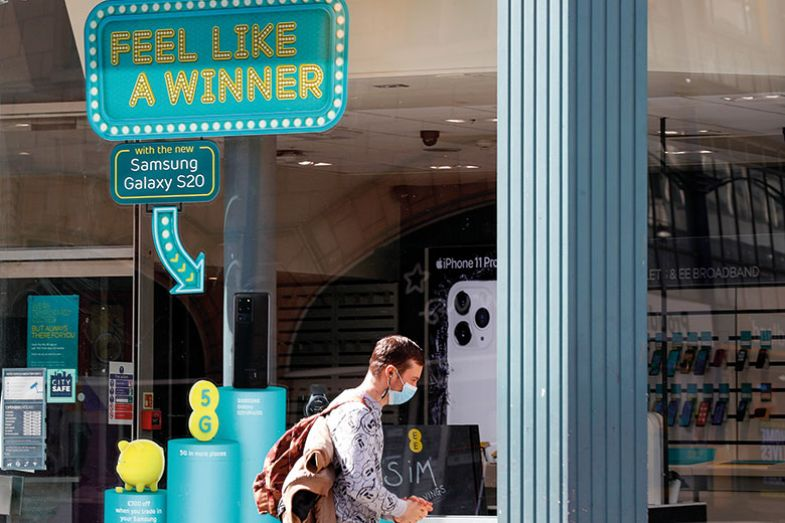pedestrian, wearing a protective mask, walks past a window with feel like a winner sign.