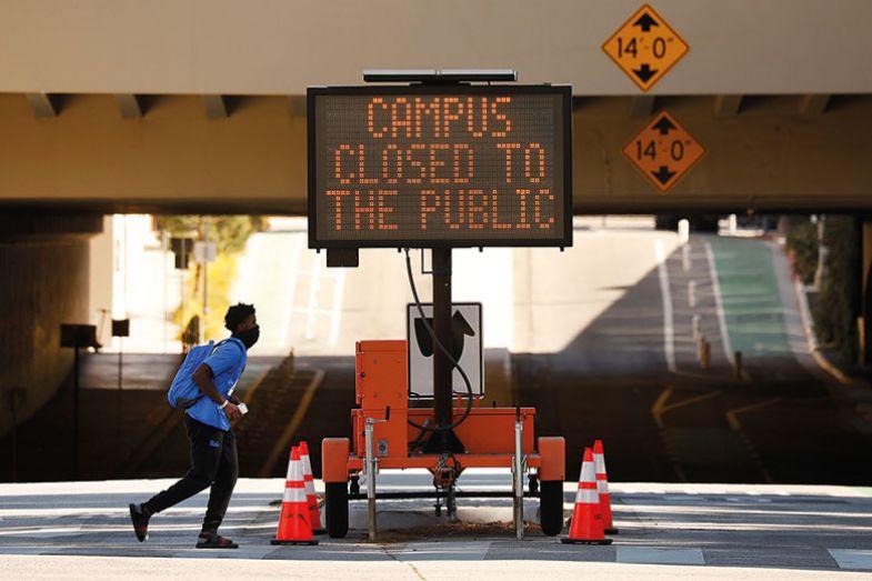 Person walks past Campus Closed to public sign.