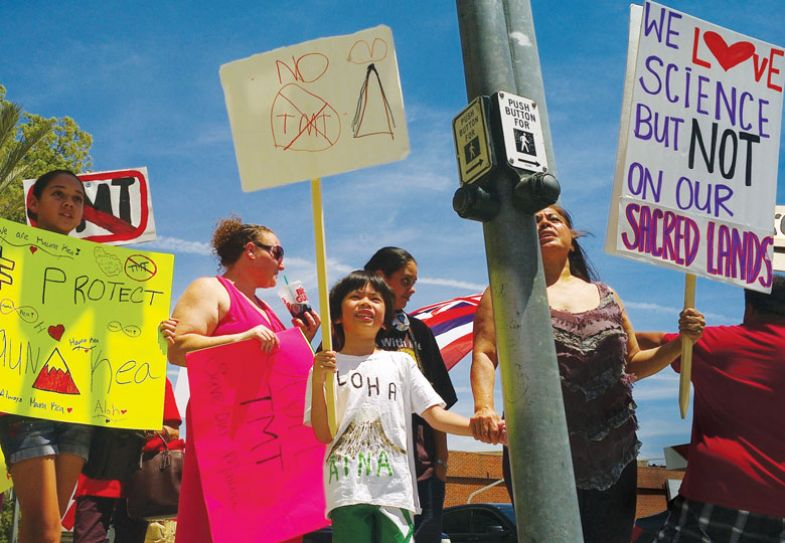 Activists protest a planned telescope for Moana Kea on the Big Island of Hawaii in front of the Thirty Meter Telescope (TMT)  as mentioned in the copy.