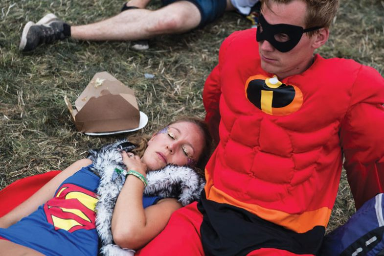 A woman dressed as Superwoman sleeps next to her partner dressed as Mr Incredible as a metaphor for unwinding the madness