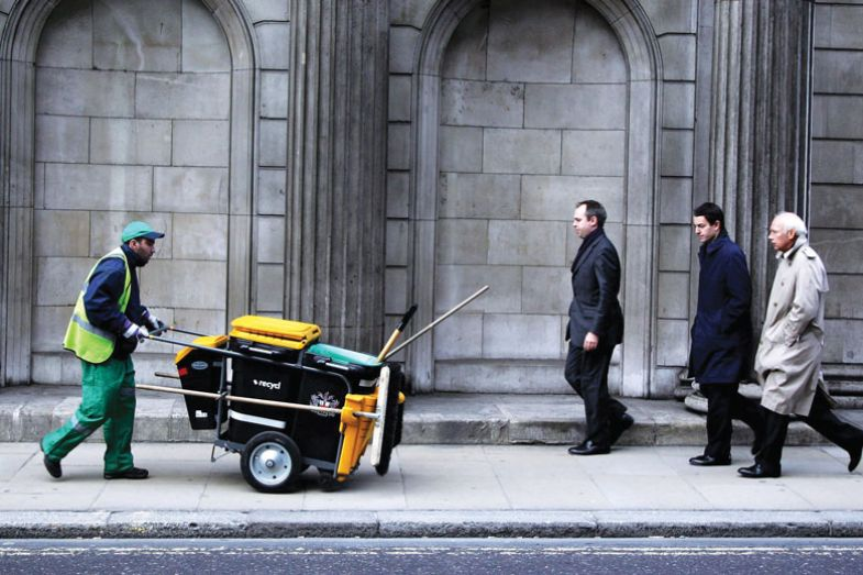 Man pushing dust cart in city for book, The Sum of Us: What Racism Costs Everyone and How We Can Prosper Together