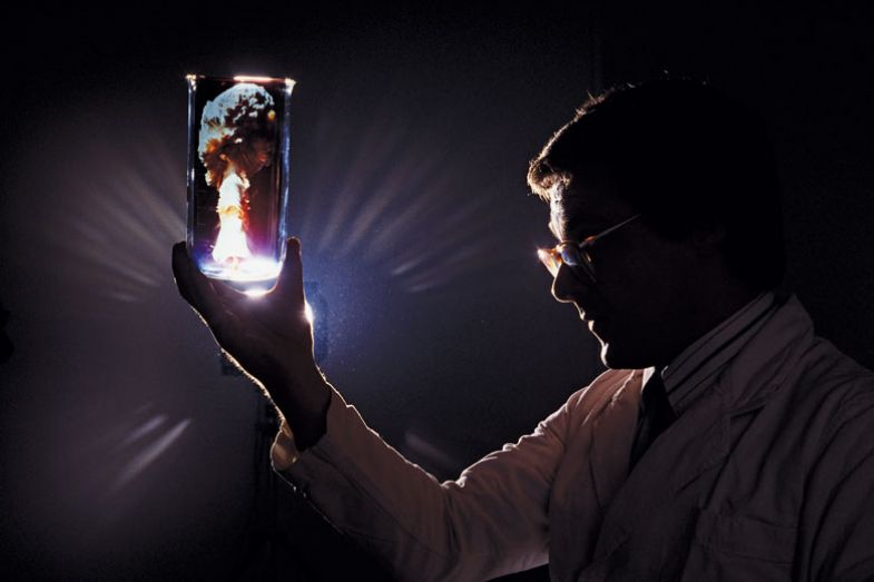 A scientist holds up a test tube in which we see a mushroom cloud, a symbolic image for nuclear cold fusion.