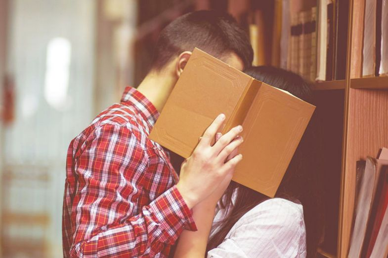 Photo of man and woman kissing in library and close their face by book for Getting back to the stacks.