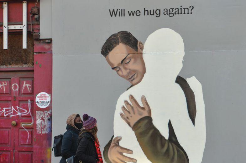 people walking past A mural 'Will we hug again?'