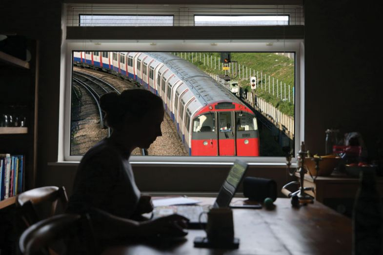 Person from home with a tube train outside the window.