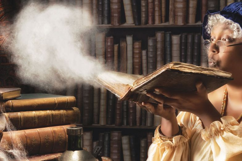 Medieval alchemist blowing dust off an old book
