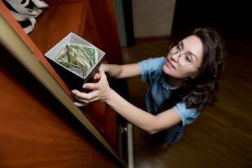 A woman takes a stash of money from the top shelf of a cupboard