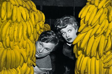 Man and woman peer out from behind bunches of bananas