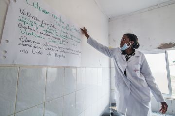 Bie, Angola - October 23, 2013 A midwife puts a poster in the wall of a public hospital about early detection and support to victims of gender based violence