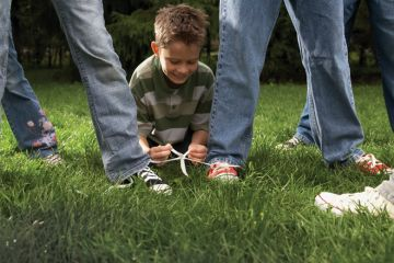 Boy ties two people's shoes laces together