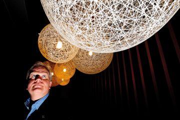 Nobel laureate Brian Schmidt looking up at lit up spheres