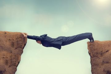 Man in a suit bridging a chasm, symbolising gaps in graduate earnings outcomes