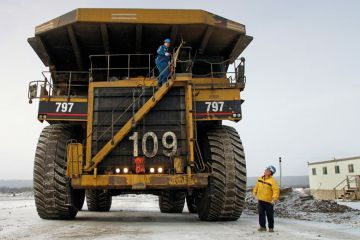 Canadian workmen operating large construction vehicle