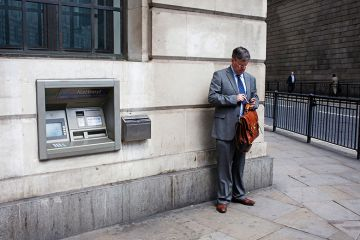 Man standing next to cash machine