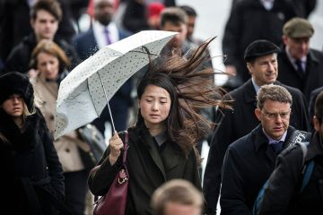 Asian woman holding umbrella on windy day
