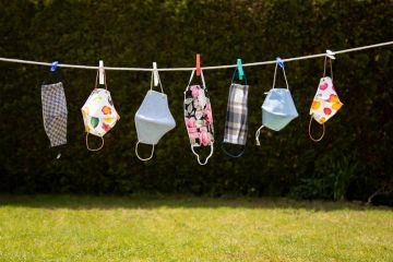 Colourful coronavirus masks in the garden hung up on a washing line