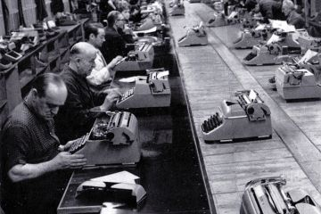 Men typing in a row in a factory