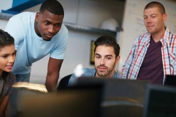 Group of students looking at computer monitor