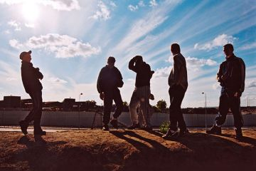 Group of teenage boys hang out on wasteland