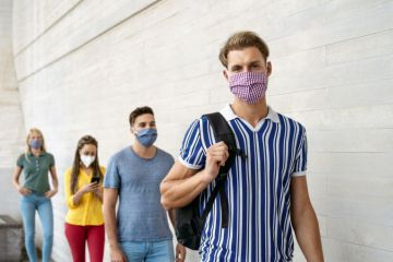students wearing face masks in queue
