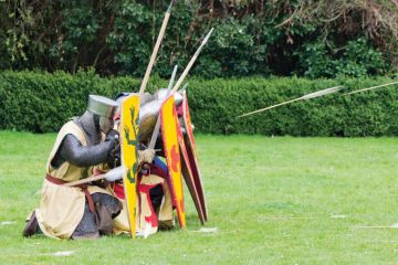Knights seeking cover from arrows behind shields