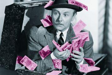 Man crouching in box full of cash