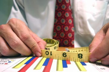 Man measuring bar graphs with tape measure