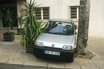 Man reverses his car into a narrow space