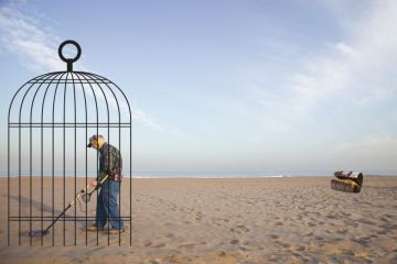 Man with a metal detector in a cage