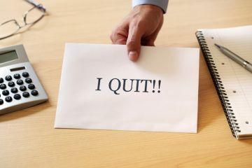 Man's hand holding 'I quit' resignation note