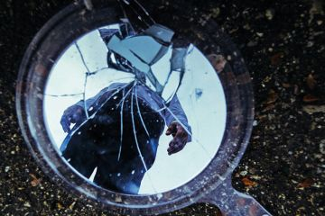 Reflection of man in cracked mirror