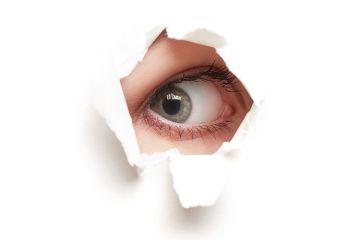 Person's eye peeping through hole