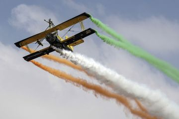 Biplane trailing coloured smoke