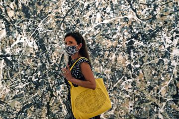 Woman in mask walking past a Pollock painting