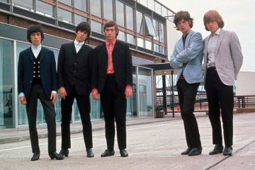 Rolling Stones posing beside airport runway