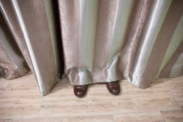 Shoes visible beneath curtain