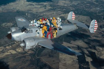Skydivers holding on to aeroplane in flight